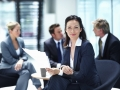 Smiling business woman with executives discussing